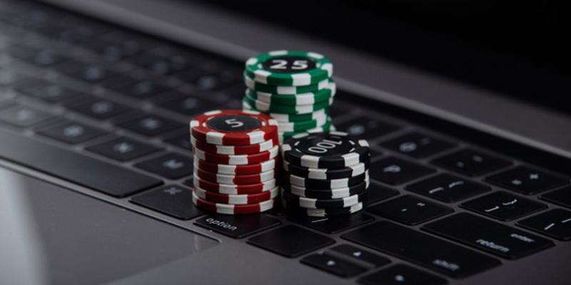Nešiojamas kompiuteris ir žetonai ant jo - pokeris Lietuvoje iš tikrų pinigų online